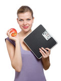 Woman holding a weight scale and red apple stock photography