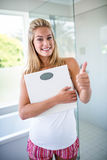 Woman holding a weighting scale with thumbs up Stock Photo