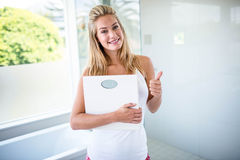 Woman holding a weighting scale with thumbs up Royalty Free Stock Photo