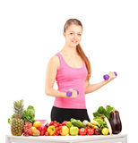 Woman holding weights and table full of food Royalty Free Stock Photos