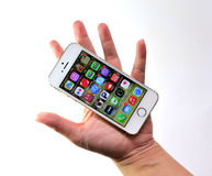 Woman holding white Apple iPhone 5S Stock Images