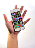 Woman holding white Apple iPhone 5S Stock Photo