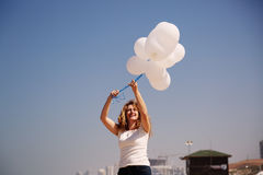 Woman holding white balloons Stock Photography