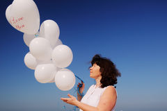 Woman holding white balloons Stock Images