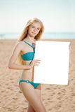 Woman holding white blank poster on the beach Stock Photo