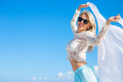 Woman holding white fabric on bright summer day with clear blue sky background Stock Images
