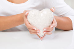 Woman holding a white heart - medical assistant Stock Photo