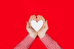 Woman holding white heart on red. Background Royalty Free Stock Photos
