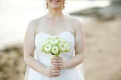 Woman holding white lotus bouquet. Bride holding white lotus flower wedding bouquet with sea in background Stock Images