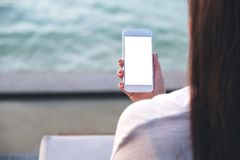 A woman holding white mobile phone with blank desktop screen by the sea and blue sky background royalty free stock photo