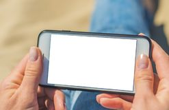 A woman holding a white mobile phone with a blank screen royalty free stock image