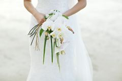 Woman holding white orchid wedding bouquet with beach background Royalty Free Stock Photos