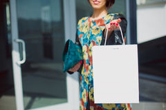 Woman holding a white paper shopping bag, with space for text. Retail shopping concept. Woman holding a white paper shopping bag, with space for text. Selective Stock Photos