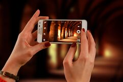 Woman Holding a White Samsung Galaxy Android Smartphone Taking a Photo of Hallway Stock Images