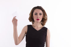 Woman holding a white sheet of paper. Studio shot Stock Images