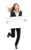 Woman holding white sign - funny and energetic. Blank sign business woman. Funny full length of young woman holding white empty billboard or placard. Beautiful Royalty Free Stock Photo