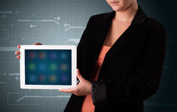 Woman holding a white tablet with blurry apps Stock Photo