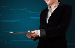 Woman holding a white tablet with blurry apps Stock Photography