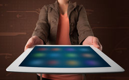 Woman holding a white tablet with blurry apps Stock Photos