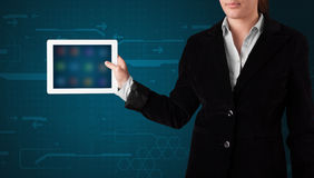 Woman holding a white tablet with blurry apps Stock Images