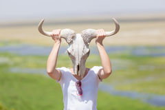 Woman holding a white wildebeest skull wearing it like a mask in nature on african wildlife safari. stock photos