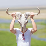 Woman holding a white wildebeest skull wearing it like a mask in nature on african wildlife safari. Royalty Free Stock Photo