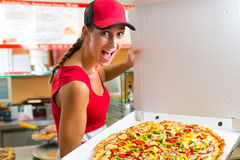 Woman holding a whole pizza in hand Stock Photos