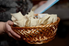 Woman holding a wicker basket with a cloth packets. Stock Photos