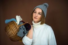 Woman holding basket with hats and scarfs Royalty Free Stock Photos