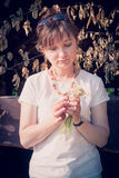 Woman holding wild flowers. With dried leaves at background Royalty Free Stock Photography