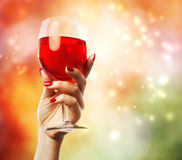 Woman holding a wine glass. On abstract lights background stock photography