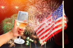 Woman holding a wine glass celebratory fireworks on the background of the US flag royalty free stock photos