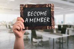 Become a member on chalkboard. A woman holding wooden blackboard with text become a member ,office background royalty free stock images