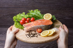 Woman holding a wooden plank with raw salmon. Raw salmon steaks on wooden board. Lettuce leaves, spices, lemon slices on a wooden board. Woody background. view stock photos