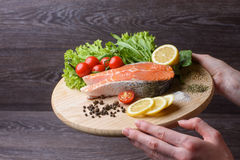 Woman holding a wooden plank with raw salmon. Raw salmon steaks on wooden board. Lettuce leaves, spices, lemon slices on a wooden board. Woody background. view royalty free stock photography