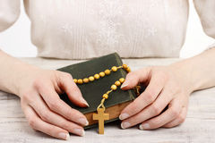 Woman holding wooden rosary and Holy Bible. Royalty Free Stock Photo