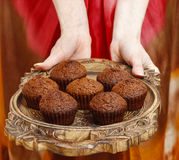 Woman holding a wooden tray with chocolate muffins Stock Image