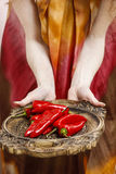 Woman holding wooden tray with ripe red hot chili peppers Stock Image