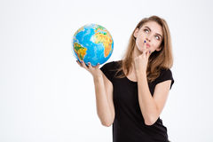 Woman holding world globe and looking up. Portrait of a thoughtful woman holding world globe and looking up isolated on a white background royalty free stock photo