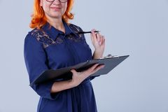 Woman holding a writing pad close-up on a gray background. A woman in age with red hair in a blue dress is holding a tablet for papers close-up on a gray Stock Image