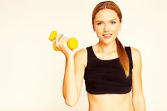 A woman holding a yellow dumbbell. Engaged in fitness Royalty Free Stock Image