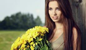 Woman holding yellow flowers Stock Photo
