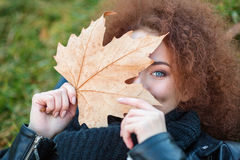 Woman holding yellow leave outdoors Royalty Free Stock Photo