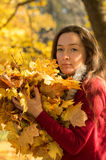 Woman holding yellow maple leafs at autumn forest Stock Image