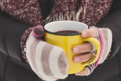 Woman holding yellow mug of hot chocolate outdoors Stock Image