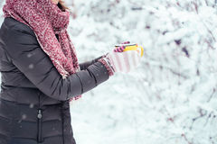 Woman holding yellow mug of hot chocolate outdoors Royalty Free Stock Photos