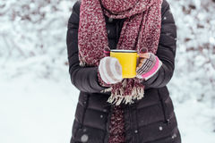 Woman holding yellow mug of hot chocolate outdoors Stock Photography