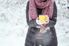 Woman holding yellow mug of hot chocolate outdoors Royalty Free Stock Images