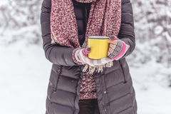 Woman holding yellow mug of hot drink outdoors. On winter day Royalty Free Stock Photos