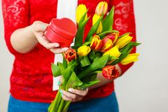 Woman holding yellow and orange bouquet of tulips royalty free stock image